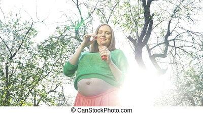 Pregnant woman blowing soap bubbles outdoor