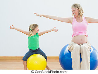 Pregnant woman bouncing on exercise ball with young daughter...