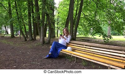 Pregnant woman chatting on cell phone while sitting on park bench outdoors.