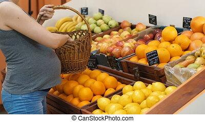 Pregnant Woman Chooses a Fruits at the Market