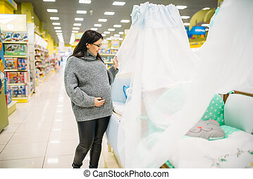 Pregnant woman choosing baby cot in store. Future mother in ...