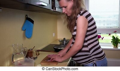 Pregnant woman chopping fresh meat with knife on cutting board