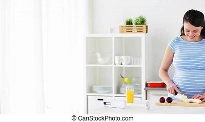 pregnant woman chopping fruits at home kitchen