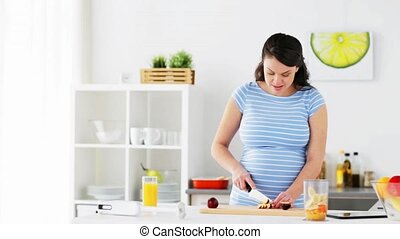 pregnant woman chopping fruits at home kitchen - healthy...