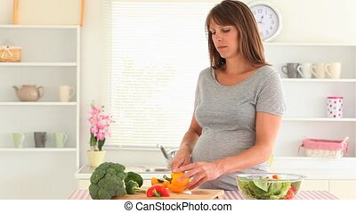 Pregnant woman chopping vegetables