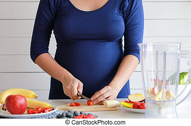 pregnant woman cooking and cutting fruit for fruit blender, healthy