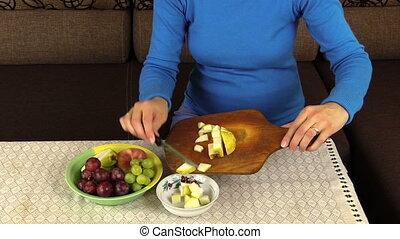 pregnant woman cut pear