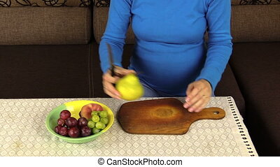 pregnant woman cut pear