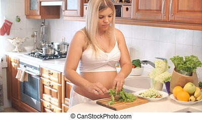 pregnant woman cuts the lettuce on wooden Board in the kitchen