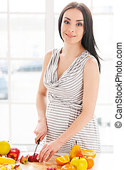 Pregnant woman cutting fruits. Cropped image of pregnant woman making a fruit salad and smiling