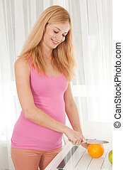 Pregnant woman cutting orange