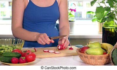 Pregnant woman cutting radish vegetables on cutting board