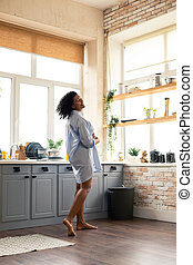 Pregnant woman dancing in her kitchen in the morning.