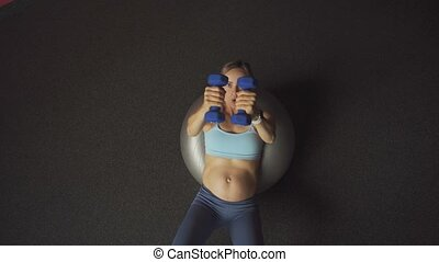 Pregnant woman doing exercises with dumbbells on pilates ball. Fitness for pregnant women concept.