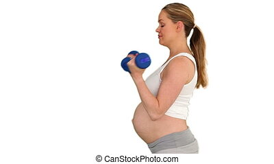 Pregnant woman doing sport bodybuilding against a white...
