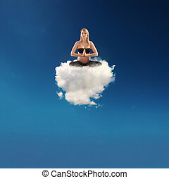 Pregnant woman doing yoga on a cloud - Pregnant young woman...