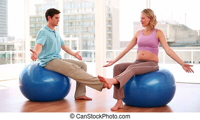 Pregnant woman doing yoga with a trainer