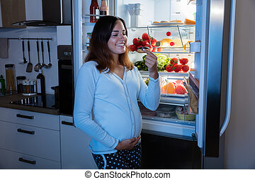 Pregnant Woman Eating Donut In Kitchen
