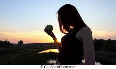 Pregnant woman eating fresh green apple at sunset.