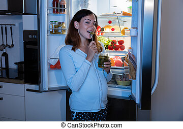 Pregnant Woman Eating Pickle In Kitchen