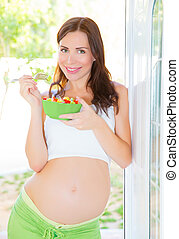 Pregnant woman eating salad