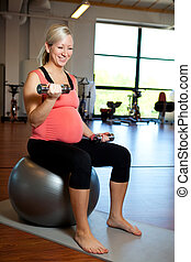 Pregnant woman exercising with weights - A pregnant woman ...