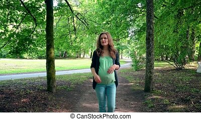 Pregnant woman expectant mother walking through park tree...