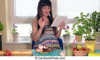 Pregnant woman feeling hunger. Future mother with tablet...