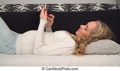 pregnant woman flipping a smart phone