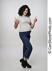 Pregnant woman gesturing thumb up - Pregnant woman standing...