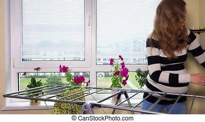 Pregnant woman hang laundry at home. Static closeup shot. 4K...