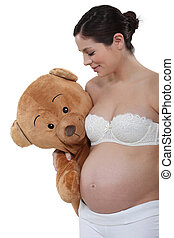 Pregnant woman holding a big teddy bear
