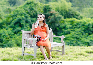 Pregnant woman holding a bottle of water in nature outdoor.