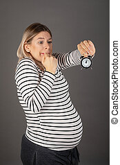 Pregnant woman holding a clock