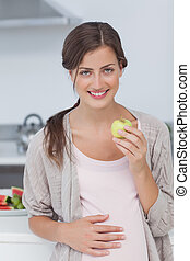 Pregnant woman holding a green apple