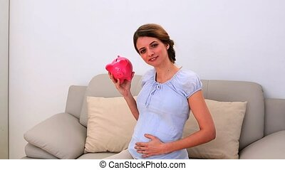 Pregnant woman holding a piggy bank on the sofa at home in...