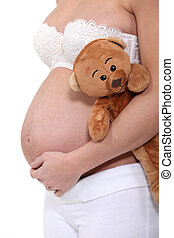Pregnant woman holding a teddy bear