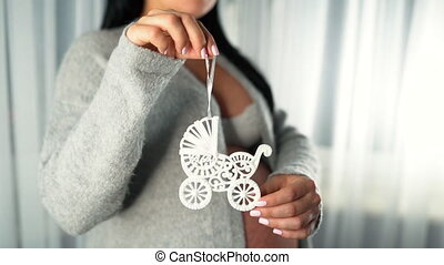 Pregnant woman holds the symbol of maternity - toy baby pram...