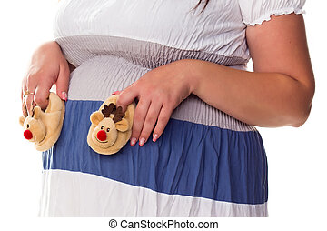 Pregnant woman holing baby's bootees at her belly isolated ...