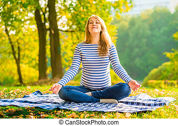 Pregnant woman in a lotus position performs breathing exercises