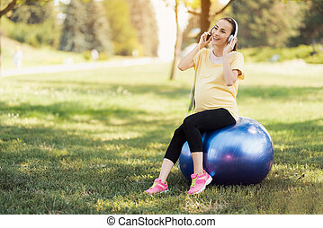 Pregnant woman in a yellow T-shirt sits on a ball for yoga and listens to music