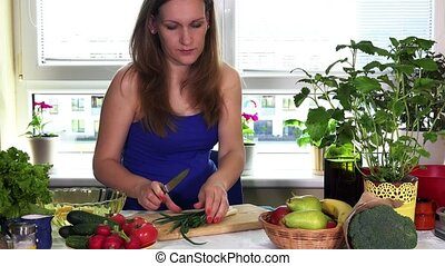 Pregnant woman in kitchen prepare fresh salad from onion and organic vegetables