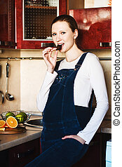 Pregnant woman in kitchen with  chocolate bar smiling