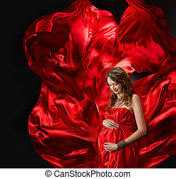 Pregnant woman in red evening dress flying on wind
