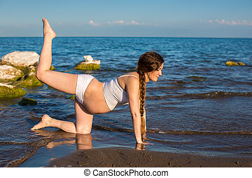 Pregnant woman in sports bra doing exercise in relaxation on yoga pose on sea.  The concept of health and sport