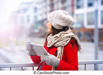 Pregnant woman in winter with digital tablet
