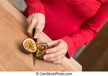 Pregnant woman is cutting a passion fruit