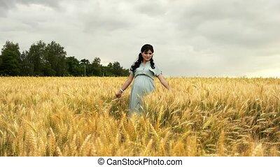 Pregnant woman is walking in summer wheat field in slow motion