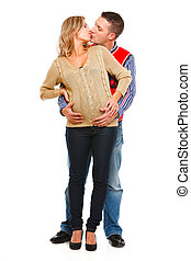 Pregnant woman kissing husband isolated on white