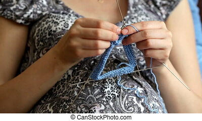 Pregnant woman knitting for baby during pregnancy. , knitting process